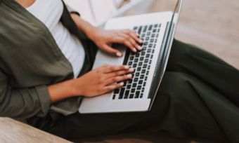 Woman using laptop on staircase