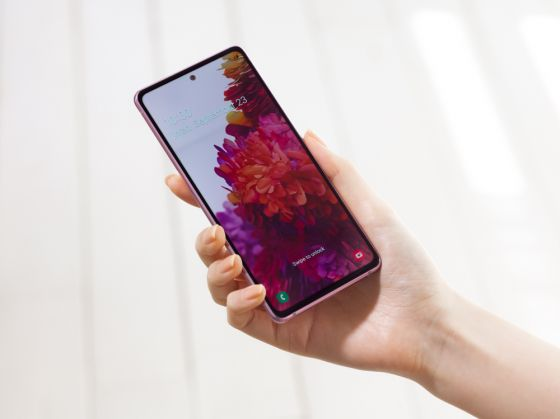 A Samsung Galaxy S20FE phone being held, with the screen turned on with a flower background