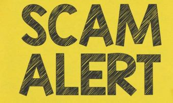 Scam alert warning text on yellow background and wood table