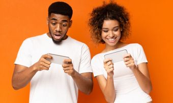 Happy young couple looking at phones together