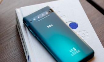 TCL 10 Pro smartphone in green colourway lying on table with book and mug