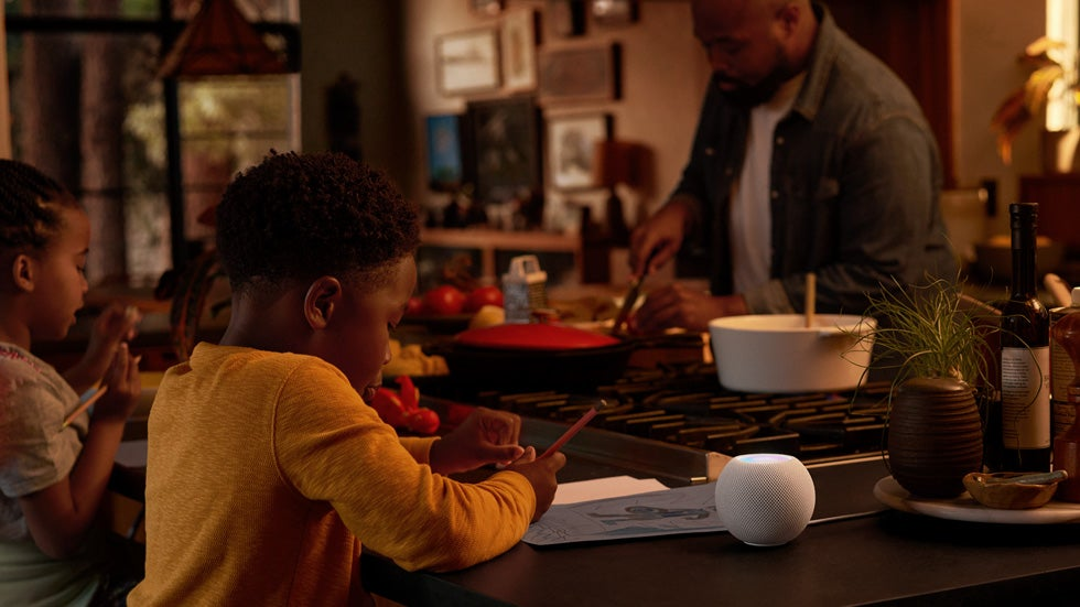 The Apple Homepod mini being used in a kitchen while two children draw and a father cooks