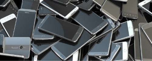 Several used phones piled up, ready to be recycled