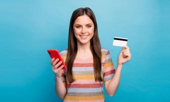 Young woman holding phone and bank card against blue background