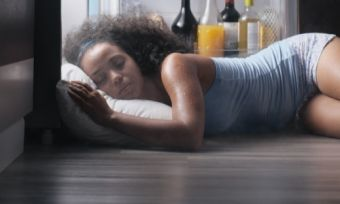 Young lady sleeping next to fridge in heatwave