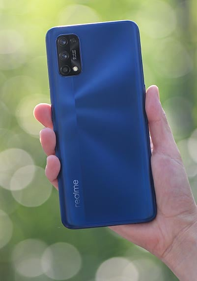 Realme 7 Pro phone in blue held in hand outside