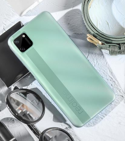 Realme C11 phone in green colour with random objects surrounding it