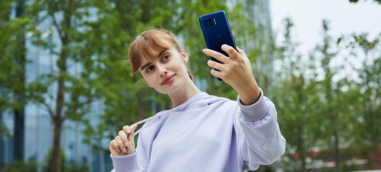 A woman taking a selfie with a Motorola phone