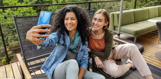 Two women sitting together and using a Motorola phone