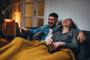 Couple laughing at TV
