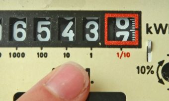 Electricity meter with finger pointing at numbers