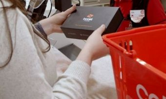 "A box with ""Boost Mobile"" written on the top, being bought from a Coles supermarket"
