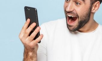 A person looking excitedly at a phone