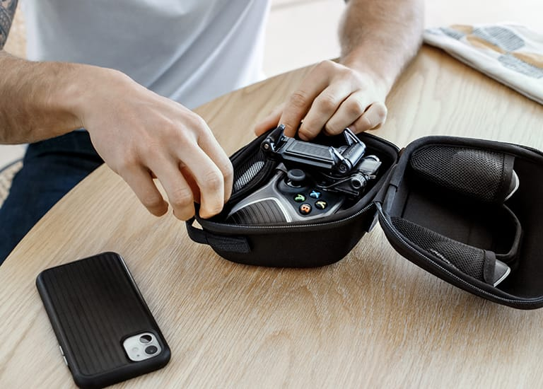 A person pulling a gaming controller out of a protective case