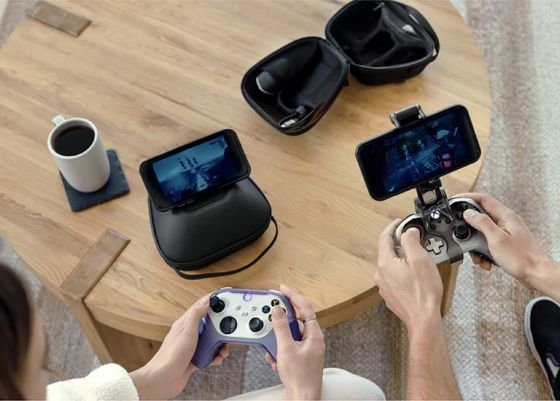 Two people using gaming controllers to play games on their phones
