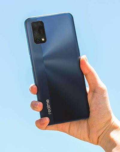 person holding Realme 7 5G phone in blue colourway