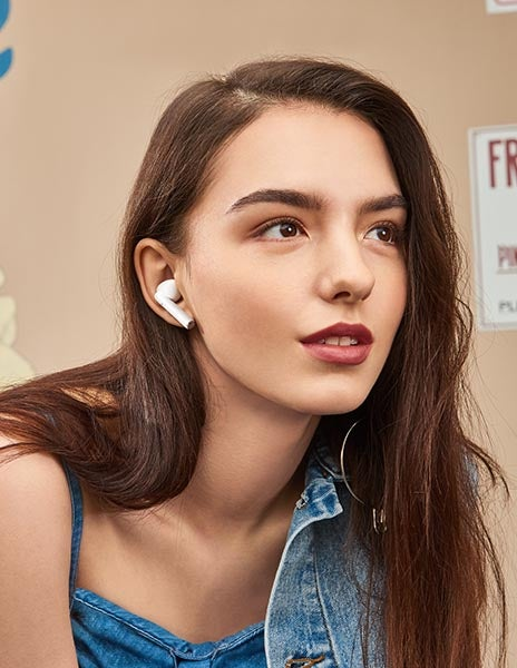 Young woman wearing Realme Buds Air Pro headphones in white