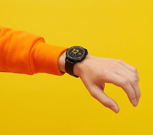 Person wearing Realme Watch S holding arm up against yellow background