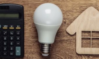 calculator, light bulb and house on wood background