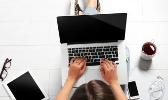 Top view of a woman using a laptop while drinking coffee