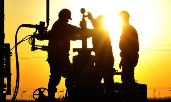 Natural gas workers working on gas pipes at sunset