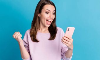 A woman in a pink top holding a phone
