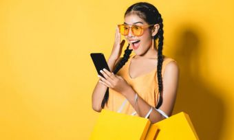 Young woman in yellow using mobile phone against yellow background