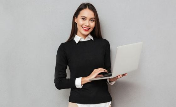 Smiling young business woman holding laptop