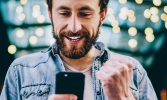 Man holding phone in excitement