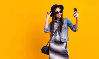 Woman looking at phone against yellow background