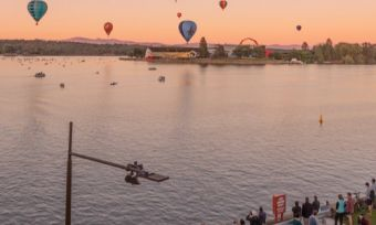 Hot air balloons over Canberra skyline at sunrise