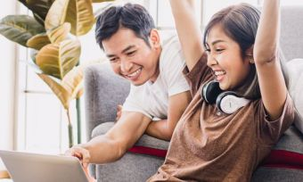 Young couple celebrate with laptop in home