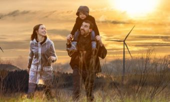 Young family outside with wind turbines in background