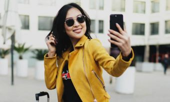 Young woman in yellow jacket using smartphone outdoors