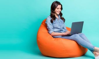 Woman looking at laptop sitting on bean bag against teal background