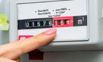 Woman hand pointing at natural gas meter
