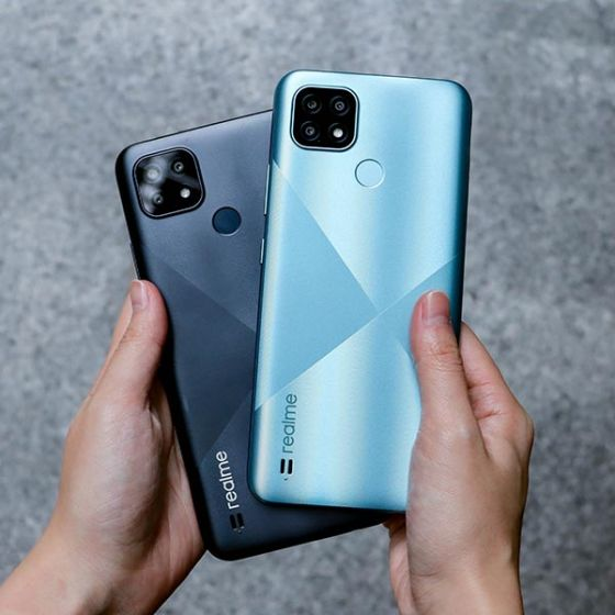 Person holding blue and black Realme C21 phones
