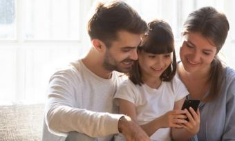 Mother, father and little girl looking at phone while sitting on sofa