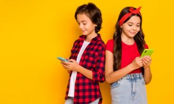 Girl and boy looking at mobile phones against yellow background