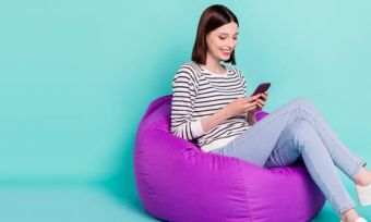 Woman looking at phone sitting on purple beanbag against teal background