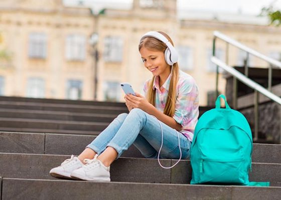 Girl looking at phone, wearing headphones and sitting on stairs with backpack