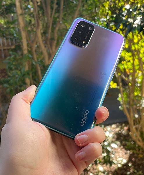 Person holding fluid purple version of OPPO A54 5G outdoors