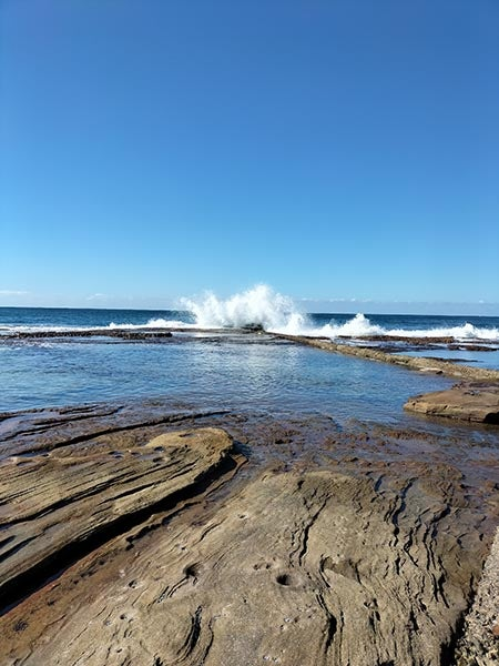 Photo of waves crashing on rock pool on clear day