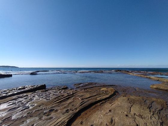 Wide angle photo of ocean and rock pools on clear day