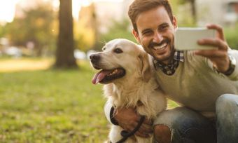 Smiling man posing for selfie with dog in park