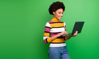Young woman holding and looking at laptop against green background