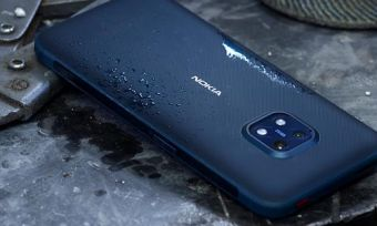 Nokia XR20 phone in blue on work bench with droplets of water on phone