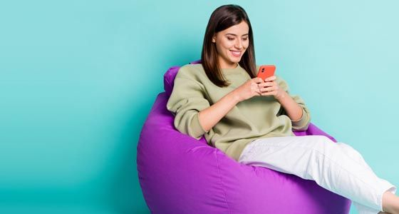 Young woman looking at mobile phone while sitting on beanbag against teal background