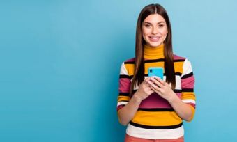 Woman holding mobile phone and smiling against blue background