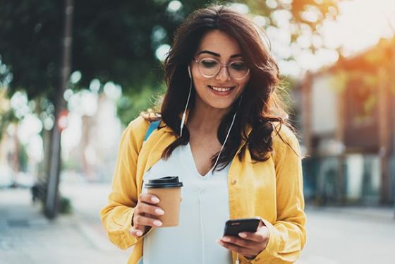 Young woman walking in city wearing headphones, looking and phone and holding coffee outdoors